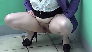 young brunette urinating in a public stairwell