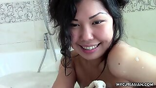Asian teen in the bathroom examines her beautiful young body.